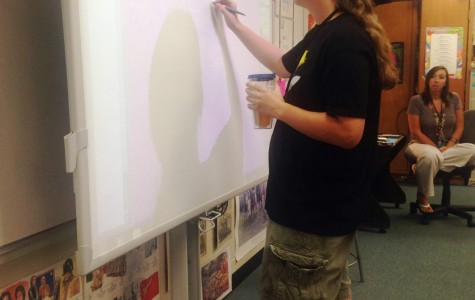 Greer High School Leo Club adviser Tabitha Pruitt supervises an officer while he writes ideas for the school year.