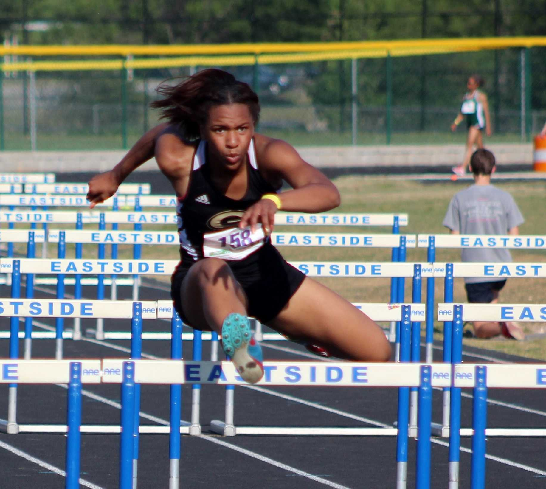 Greer High School Sophomore Kaiya Bradford clears a hurdle to finish the 100 Hurdle event at the Greenville County Track and Field Championships Wednesday night at Eastside High School.