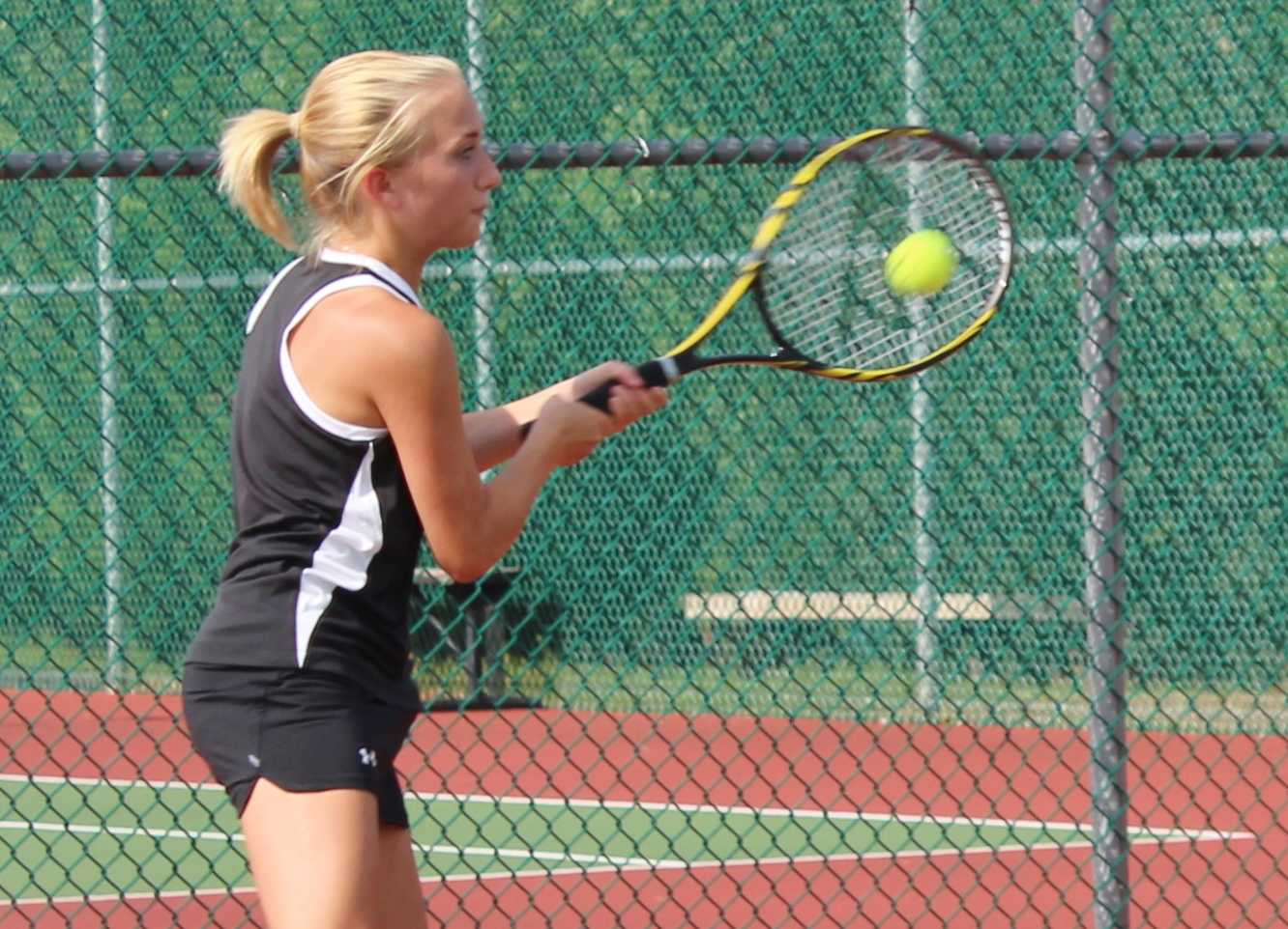 Greer High School Tennis Player Emily Swearingin returns a serve in a match this year. Swearingin helped lead the Yellow Jackets to a 4-3 victory over Powdersville Thursday night at Greer High School.
