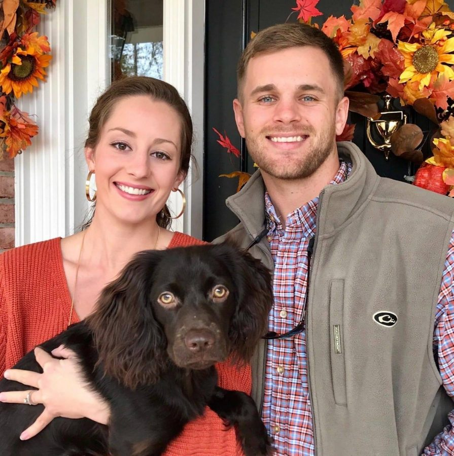 Mr. Arwood posing with his wife, Emily, and boykin spaniel, Penny.